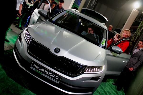 посетители презентации делают осмотр автомобиля